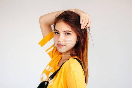 Photo pour Verticale de fille d'adolescent de sourire insouciante avec le long cheveu foncé dans le t-shirt jaune sur le fond gris - image libre de droit