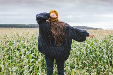 Photo pour Belle fille asiatique aux cheveux longs insouciants en chapeau jaune et pull tricoté par derrière dans le champ de maïs d'automne. Concept de sensibilité à la nature - image libre de droit