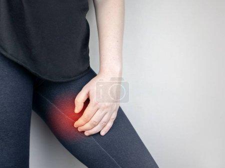 Una mujer sufre de dolor en el muslo interno. El concepto de tratar una articulación de la cadera para el trauma, miositis, deterioro del nervio endingsor osteoartritis .