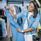 attractive young black woman in straw hat looking at blue dress in clothes shop