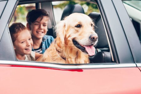 smiling little children sitting with labrador in automobile