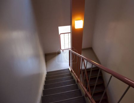 A flight of stairs in a pink hallway with a railing for safety