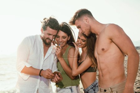 Group of friends using smartphone on beach at sunset