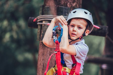 preteen boy climbing in adventure activity park with helmet and safety equipment