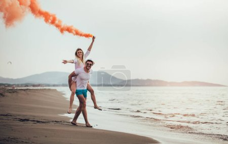 Young couple with smoking bomb in hand standing outdoors at golden summer background.
