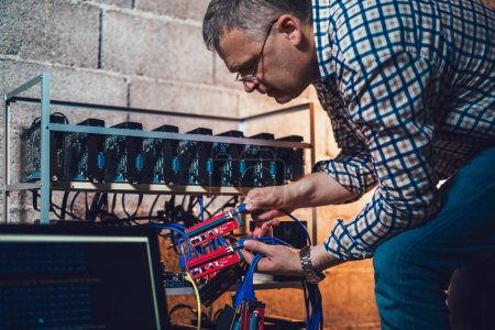 Partial view of programmer adjusting cryptocurrency mining rig to optimal operational settings