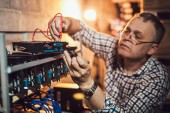 Portrait of programmer adjusting cryptocurrency mining rig to optimal operational settings