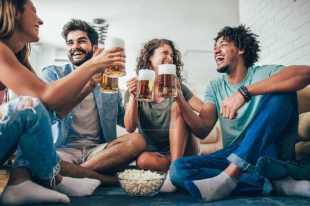 Happy friends eating popcorn and drinking beer mug at home, having fun.