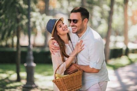 Photo pour Joyeux jeune couple s'amuser et rire ensemble en marchant avec panier dans le parc - image libre de droit