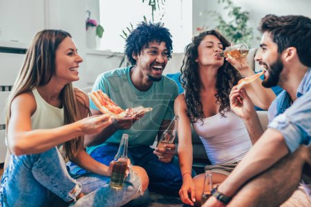 Group of young friends eating pizza and drink beer at home, home party concept