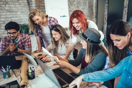 Group of young business people in smart casual wear working together in creative office