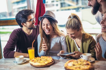 Young friends enjoying while sitting at table in pizzeria