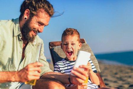 Photo pour Prise de vue de père et fils utilisant le téléphone à la plage. Jeune homme avec petit garçon utilisant un téléphone intelligent au bord de la mer . - image libre de droit