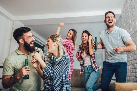 Photo pour Groupe d'amis jouer karaoké à la maison. Notion sur l'amitié, de divertissement à domicile et personnes - image libre de droit