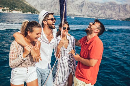 Smiling friends sailing on yacht. Vacation, travel, sea, friendship and people concept