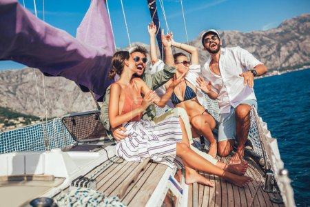 Photo for Smiling friends sitting on sailboat deck and having fun.Vacation, travel, sea, friendship and people concept - Royalty Free Image