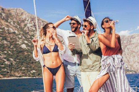 Photo pour Amis de voile sur l'yacht de sourire. Concept de vacances, voyage, mer, l'amitié et les gens - image libre de droit