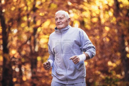 Photo for Senior runner in nature. Elderly sporty man running in forest during morning workout. Healthy and active lifestyle at any age concept - Royalty Free Image