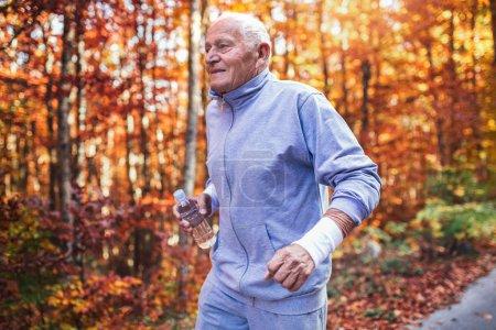 Coureur senior dans la nature. Vieil homme sportif en cours d'exécution dans la forêt au cours de la séance d'entraînement du matin. Mode de vie sain et actif chez n'importe quel concept d'âge