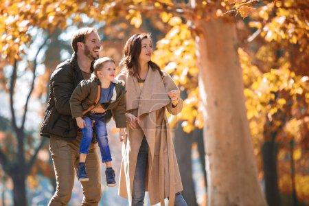 Photo pour Jeune famille s'amusant dans le parc d'automne avec son fils . - image libre de droit