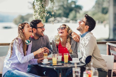 Photo for Group of four friends having fun a coffee together. Two women and two men at cafe talking laughing and enjoying their time - Royalty Free Image