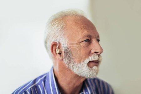 Photo pour Senior homme porter des aides auditives - image libre de droit