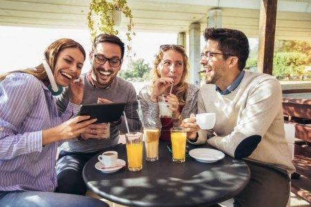 Photo pour Groupe de quatre amis s'amuser un café ensemble. Deux femmes et deux hommes au café parlent en riant et en utilisant une tablette numérique . - image libre de droit