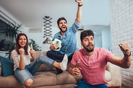 Photo for Happy friends or football fans watching soccer on tv and celebrating victory at home.Friendship, sports and entertainment concept. - Royalty Free Image
