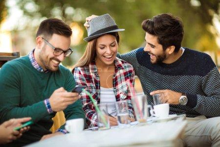 Foto de Grupo de cuatro amigos que se divierten un café juntos. Dos mujeres y dos hombres en el café hablando riendo y disfrutando de su tiempo. Uso de teléfono - Imagen libre de derechos