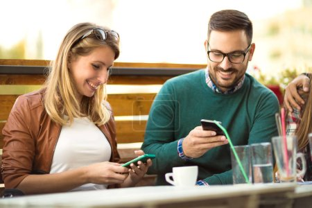 Photo for Group of four friends having fun a coffee together. Two women and two men at cafe talking laughing and enjoying their time. Using phone - Royalty Free Image