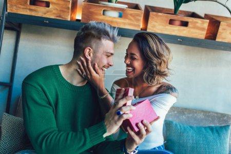 Photo pour Jeune homme présentant un cadeau à une petite amie afro-américaine dans un café - image libre de droit