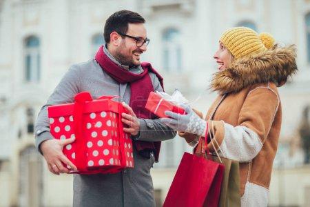 Foto de Joven pareja vestida con ropa de invierno con cajas de regalo al aire libre. - Imagen libre de derechos