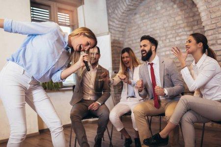 Photo pour Gens d'affaires faisant équipe exercice d'entraînement au cours de team building séminaire chant karaoké. - image libre de droit