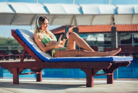Photo pour Portrait de jeune femme sous le soleil tropical près de piscine sur une chaise longue à l'aide de tablette numérique - image libre de droit