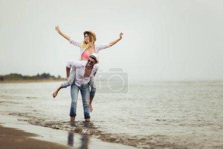 Photo pour Joyeux couple amoureux pendant les vacances d'été à la plage. Joyeuse fille piggyback sur jeune copain avoir du plaisir . - image libre de droit