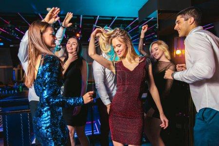 Photo pour Les jeunes gens heureux dansent au club. Vie nocturne et concept de discothèque . - image libre de droit