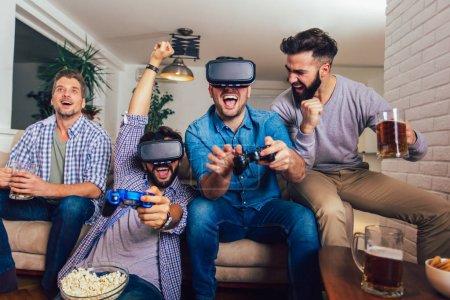 Photo pour Des amis heureux jouant à des jeux vidéo avec des lunettes de réalité virtuelle - Les jeunes s'amusent avec une nouvelle console technologique en ligne - image libre de droit