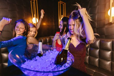 Photo for Happy women clinking champagne glasses and celebrating at night club - Royalty Free Image