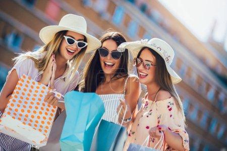 Foto de Chicas jóvenes felices caminando por la calle con bolsas de compras. Compras felices con sonrisas . - Imagen libre de derechos
