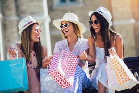Photo pour Trois belles filles en lunettes de soleil avec des sacs à provisions en ville . - image libre de droit