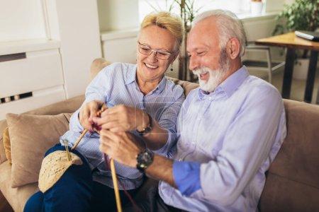 Photo pour Femme âgée enseignant à son mari l'art de tricoter des vêtements en laine . - image libre de droit