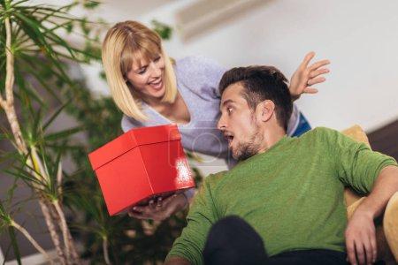 Photo pour Homme heureux recevant un cadeau de sa petite amie alors qu'il était assis sur le canapé - image libre de droit