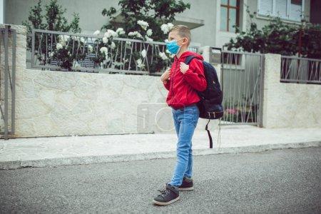 Photo pour Portez un masque facial pendant l'éclosion de coronavirus et de grippe. Le garçon porte un masque avant d'aller à l'école pour prévenir l'épidémie Maladies infectieuses et poussière dans l'air . - image libre de droit