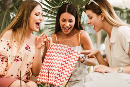 Photo for Three young women in a cafe after a shopping - Royalty Free Image
