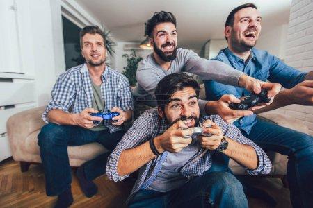 Photo pour Souriant amis masculins jouer à des jeux vidéo à la maison et avoir du plaisir. - image libre de droit