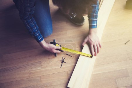 Male hands working with wooden plank and measuring tape