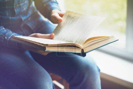 Photo pour Vue partielle de l'homme assis sur la chaise de lecture livre - image libre de droit