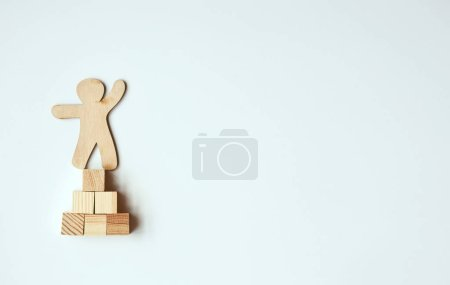 Little wooden man on top of blocks as mountain symbol. Business, success, leadership and achievement concept