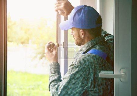 Foto de Hombre de servicio de instalación de ventana con destornillador - Imagen libre de derechos