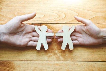 Photo pour Couple tenant dans les mains des hommes jouet en bois comme symbole d'amour et d'amitié - image libre de droit